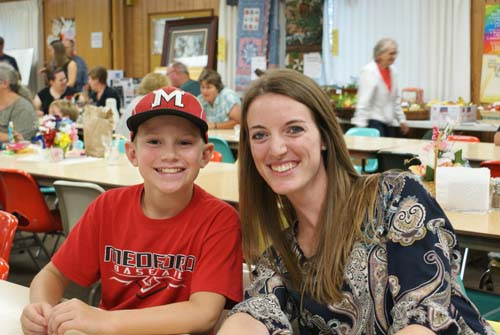 Julie and little boy smile for the camera at Good Shepherd fall fest