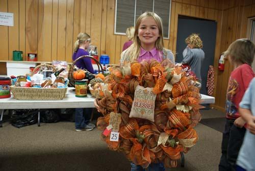 little girl shows off fall wreath won at Good Shepherd fall fest