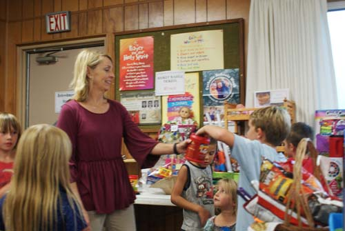 children take turns drawing names for winners of baskets at fall fest