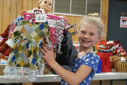 little girl is thrilled with doll basket she won at fall fest