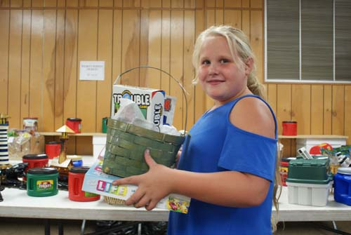 young girl shows off basket she won at Good Shepherd fall fest