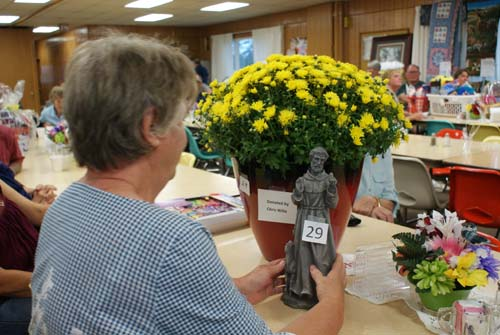 Laura admires pot of mums and statue from Good Shepherd fall fest raffle