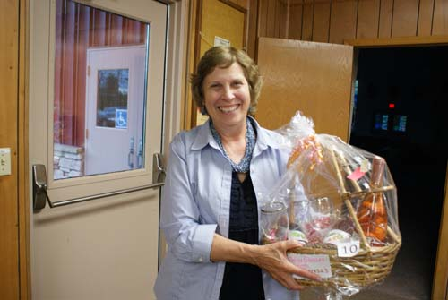 smiling Bev shows off the basket she won at Good Shepherd fall fest