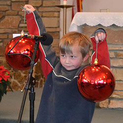 Christmas pageant boy holding ornaments image