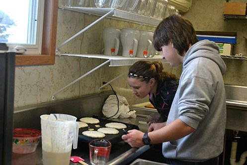 students-check-out-pancakes-on-griddle-image
