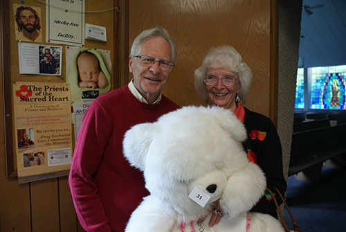 happy couple wins stuffed bear