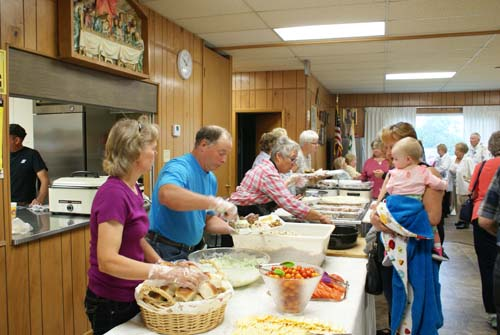 volunteers serve food at Good Shepherd fall fest dinner