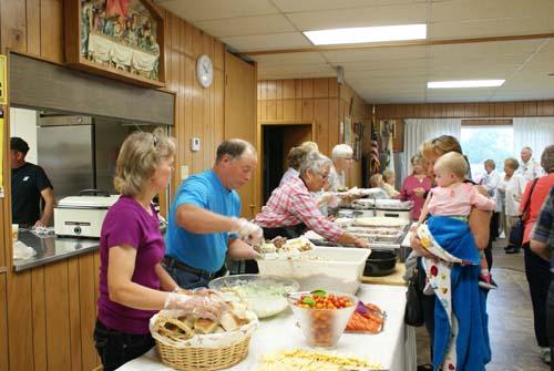 volunteers serve food at Good Shepherd fall fest dinner