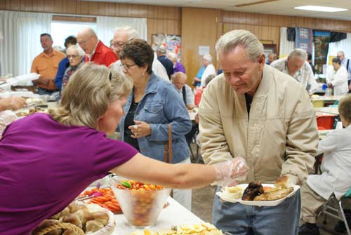 Joan serving Joe at Good Shepherd fall fest dinner