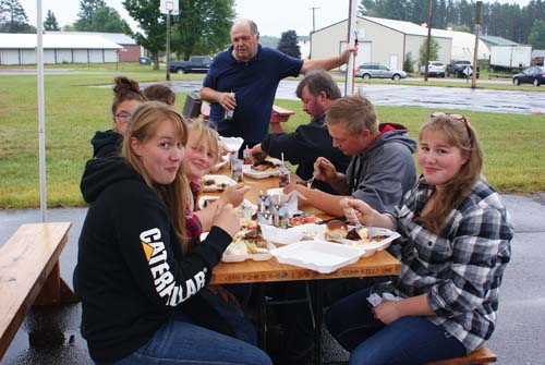 a table full of happy diners on a picnic table outside at Good Shepherd fall fest