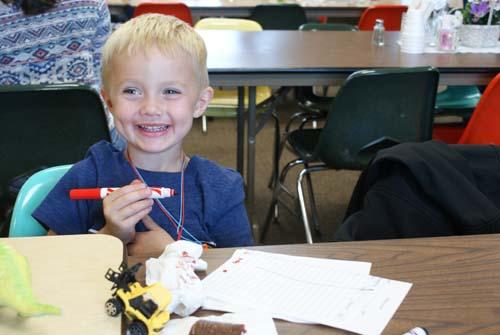 little boy plays bingo at Good Shepherd fall fest