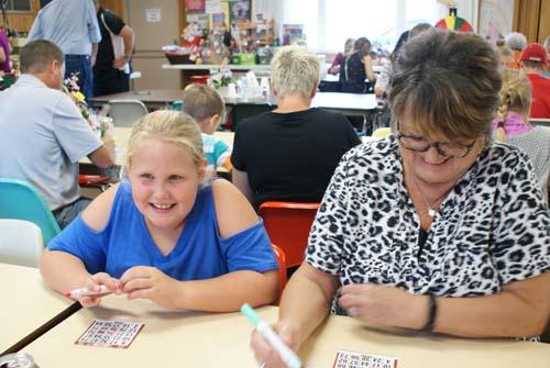 little girl plays bingo next to Jan at Good Shepherd fall fest