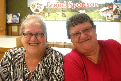 two smiling ladies help prepare for Good Shepherd fall fest