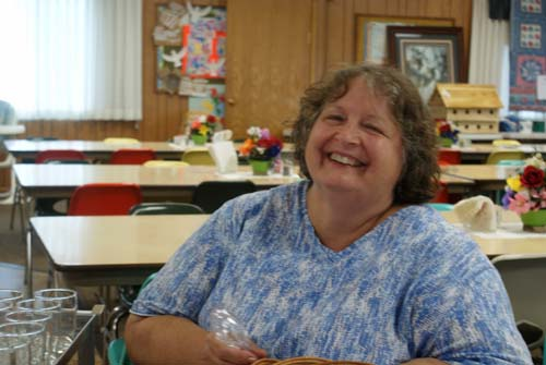 happy lady helps with setting up tables for Good Shepherd fall fest dinner