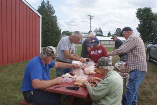 group of workers cleaning chicken for Good Shepherd fall fest dinner