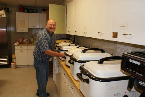 Ted shows off a row of roasters full of meat for Good Shepherd fall fest dinner