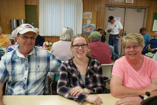 Tom and Emily and Debbie smile for a family picture at Good Shepherd fall fest