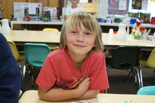 little boy smiles for the camera at Good Shepherd fall fest