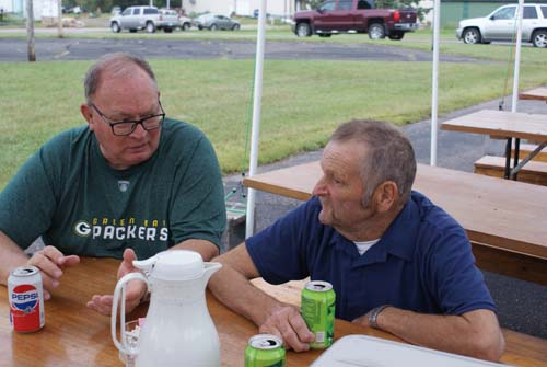 two guys sitting on picnic table outside at Good Shepherd fall fest
