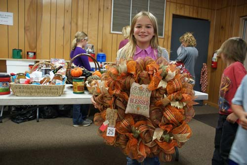 little girl shows off fall wreath won at Good Shepherd fall fest