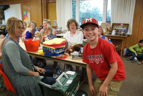 young man is thrilled with fishing basket he won at fall fest