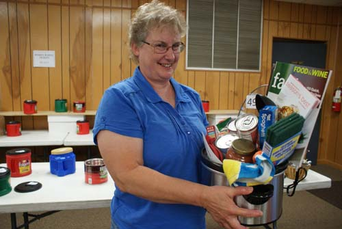 Cathy wins a basket full of cooking items at Good Shepherd fall fest raffle