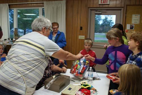 children gather round to help Deb draw a winner of big jar of candy